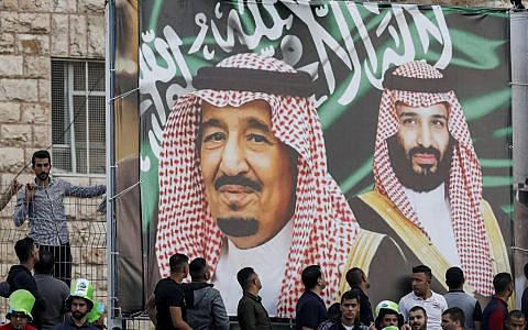 Football fans stand beneath a large banner depicting Saudi King Salman bin Abdulaziz (C) and his son Crown Prince Mohammed bin Salman (R) as they attend the World Cup 2022 Asian qualifying match between Palestine and Saudi Arabia in the town of al-Ram in the West Bank on October 15, 2019.  (Ahmad GHARABLI / AFP)