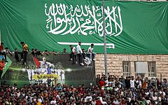 Football fans stand beneath a giant banner depicting the Saudi national flag as they attend the World Cup 2022 Asian qualifying match between Palestine and Saudi Arabia in the town of al-Ram in the West Bank on October 15, 2019. (Ahmad GHARABLI/AFP)