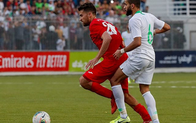 Palestine's midfielder Nazmi Albadawi (C) vies for the ball with Saudi's Mohammed Al-Breik  during the World Cup 2022 Asian qualifying match between Palestine and Saudi Arabia in the town of al-Ram in the West Bank on October 15, 2019. (Ahmad GHARABLI / AFP)