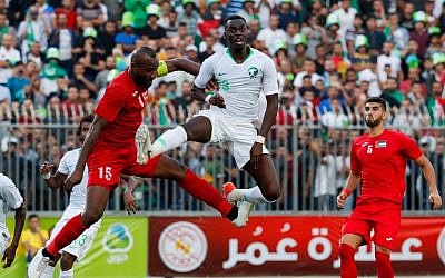 Saudi defender Ziyad Al-Sahafi vies for the ball with Palestine's defender Abdelatif Bahdari during the World Cup 2022 Asian qualifying match between Palestine and Saudi Arabia in the town of al-Ram in the West Bank on October 15, 2019. (Ahmad GHARABLI / AFP)