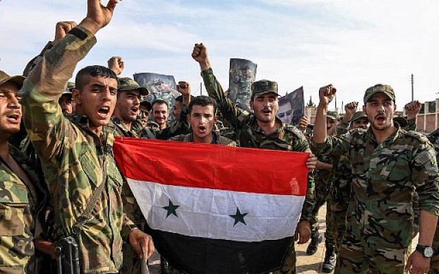 Syrian government soldiers chanting slogans as they pose for a group photo with a national flag and portraits of President Bashar Assad on the outskirts of the northern city of Manbij in the north of Aleppo province as government forces deploy there on October 15, 2019. (AFP)