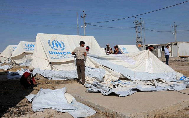 Workers set tents in preparation to receive Syrian refugees who have been newly displaced by the Turkish military operation in northeastern Syria, at the Bardarash camp, near the city of Dohuk, in Iraq's autonomous Kurdish region, on October 16, 2019. (SAFIN HAMED / AFP)