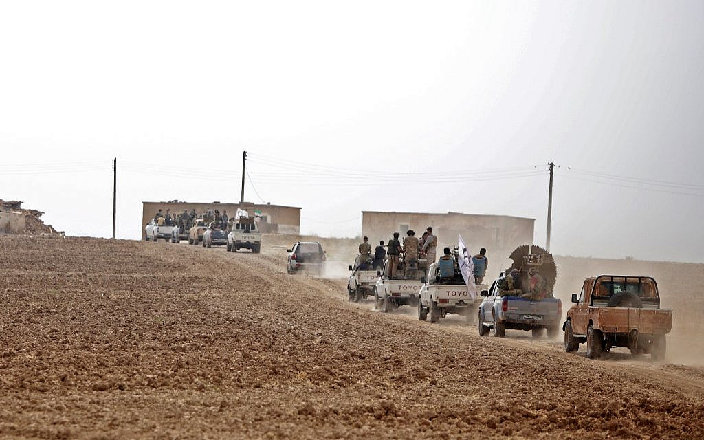 A convoy of pickup trucks transports Turkey-backed Syrian fighters on the road between Tal Abyad and Kobane on October 16, 2019 as Turkey continues its assault on Kurdish-held border towns in northeastern Syria. (Bakr ALKASEM / AFP)