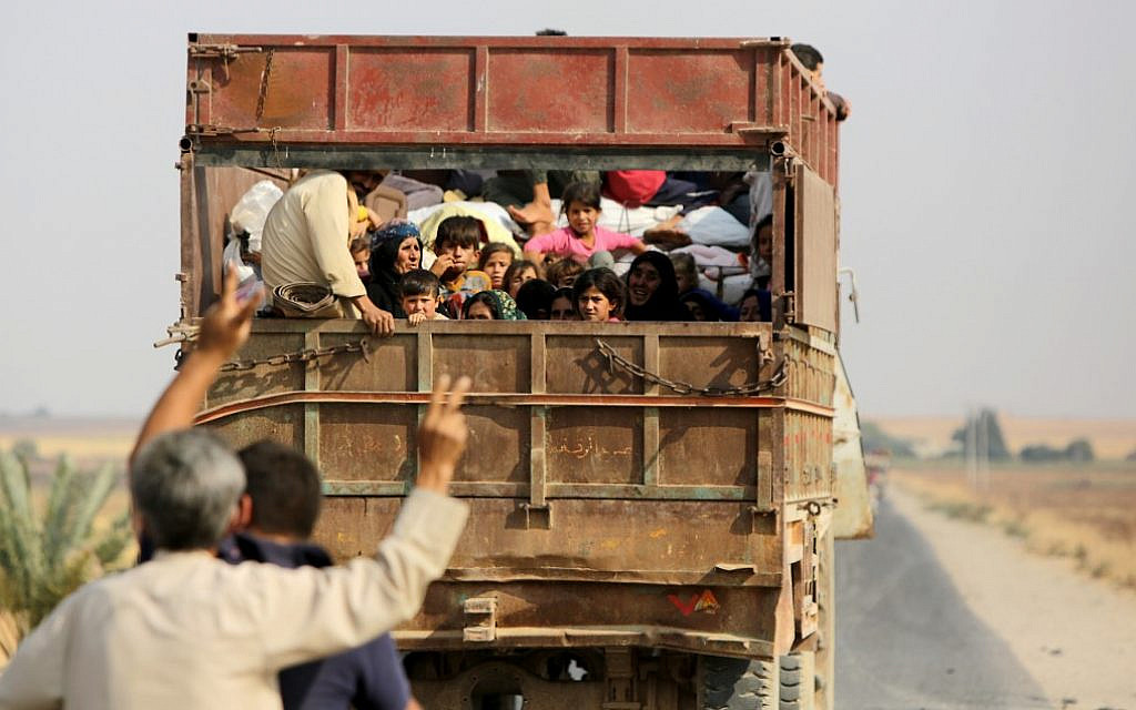 Kurdish civilians flee the town of Kobane on the Turkish border on October 16, 2019 as Turkey continues its assault on Kurdish-held border towns in northeastern Syria. (Bakr Alkasem/AFP)