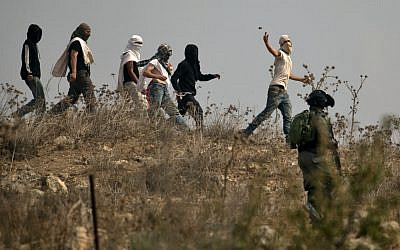 Illustrative: Israeli soldiers stand by as masked Israeli settlers throw stones at Palestinian protesters (unseen) gathering during a demonstration against construction on an Israeli outpost near the Palestinian village of Turmusaya and the settlement of Shilo, north of Ramallah in the West Bank, October 17, 2019. (JAAFAR ASHTIYEH / AFP)