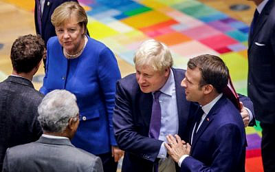 British Prime Minister Boris Johnson (2nd R) embraces French President Emmanuel Macron (R) upon their arrival for a round table meeting as part of a European Union summit at European Union Headquarters in Brussels on October 17, 2019. (Olivier Matthys / POOL / AFP)