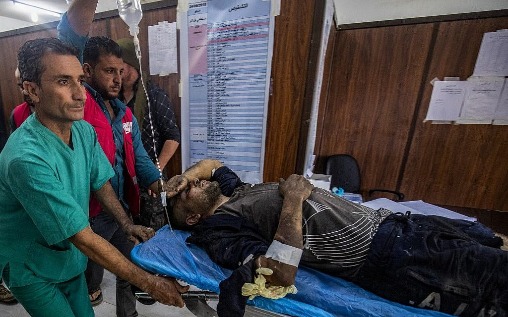 A man who was injured during the ongoing Turkish offensive against Kurdish-controlled areas of northeastern Syria lies at a hospital in Tal Tamr near the Syrian Kurdish town of Ras al-Ain