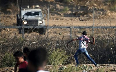 Illustrative: A Palestinian uses a slingshot to throw a stone at Israeli forces during clashes along the border with Israel, east of Bureij in the central Gaza Strip, on October 18, 2019. (Mahmud Hams/AFP)
