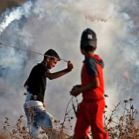 A Palestinian uses a slingshot to throw back a tear gas canister at Israeli forcesduring a riot along the border with Israel east of Bureij in the central Gaza Strip on October 18, 2019. (Mahmud Hams/AFP)