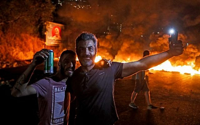 A man holds up his cell phone with the flash lighting his face as another next to him holds up a beer can while standing before a burning tire fire blocking the main Beirut-Tripoli highway, near the town of Tabarja north of the capital amidst protests against dire economic conditions on October 18, 2019. (Joseph Eid/AFP)