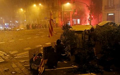 """Protesters take shelter behind garbage containers during clashes near the Police headquarters in Barcelona, on October 18, 2019, on the day that separatists called a general strike and a mass rally. - Spain's protest-hit northeast was gripped by a general strike today as thousands of """"freedom marchers"""" converged on Barcelona for a mass show of dissent over the jailing of nine Catalan separatist leaders. (Photo by Pau Barrena / AFP)"""
