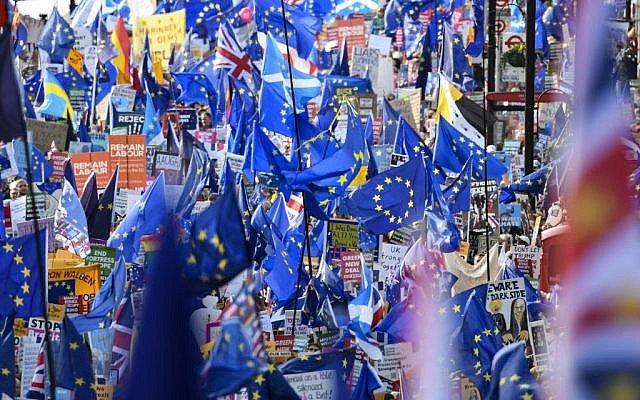 Demonstrators hold placards and EU and Union flags as they take part in a march by the People's Vote organisation in central London