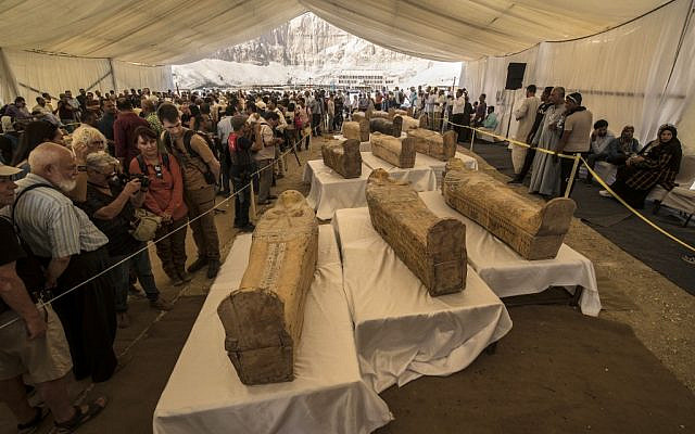 Tourists observe sarcophagi displayed in front of Hatshepsut Temple in Egypt's valley of the Kings in Luxor on October 19, 2019. (Photo by Khaled DESOUKI / AFP)