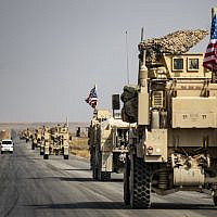 US military vehicles drive on a street in the town of Tal Tamr on October 20, 2019, after pulling out of their base. (Photo by Delil SOULEIMAN / AFP)