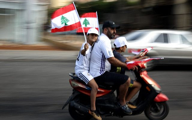 Lebanese youths wave national flags on their way to join a rally in downtown Beirut on October 20, 2019, on the fourth day of demonstrations against tax increases and official corruption. (Patrick Baz/AFP)