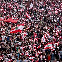 Lebanese demonstrators wave national flags as they take part in a rally in the capital Beirut's downtown district on October 20, 2019. (Patrick Baz/AFP)