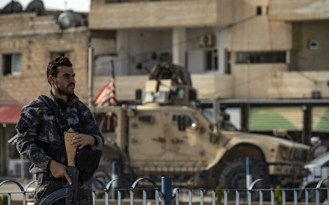 A fighter from the Syrian Democratic Forces SDF stands guard as a US military vehicle pulling out of a US forces base in the Northern Syrian town of Tal Tamr drives by, on October 20, 2019. (Delil SOULEIMAN / AFP)