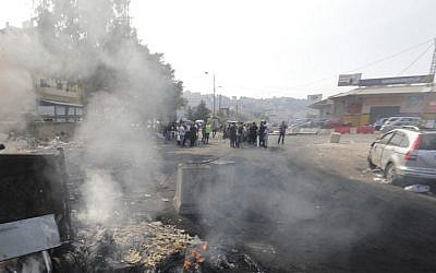 A picture taken on October 21, 2019, shows smoke billowing from a roadblock set by Lebanese protesters on a road in Zouk Mosbeh, north of the capital Beirut. (JOSEPH EID / AFP)