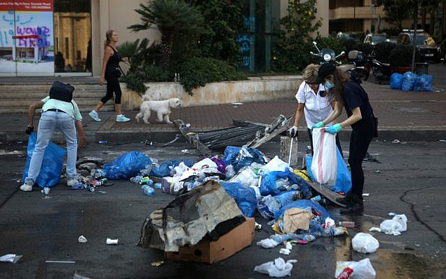Lebanese demonstrators clean up rubbish on a street in the capital Beirut's downtown district following a night of protests against tax increases and official corruption, on October 21, 2019 (Patrick BAZ / AFP)