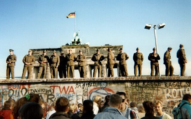 In this file photo taken on November 11, 1989, East German border guards stand on a section of the Berlin wall with the Brandenburg gate in the background in Berlin. (Gunther Kern/AFP)