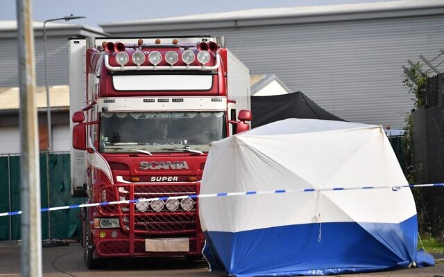 A UK police forensic tent is seen in front of a truck, believed to have originated from Bulgaria, and found to be containing 39 dead bodies, at the scene where it was discovered at Waterglade Industrial Park in Grays, east of London, on October 23, 2019. (Photo by Ben STANSALL / AFP)