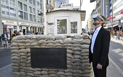 In this file photo taken on August 22, 2019 Jonas Rothe, founder and CEO of Timeride, a company offering virtual reality tours through a still-divided Berlin, poses next to Checkpoint Charlie in Berlin, Germany. (Tobias Schwarz/AFP)
