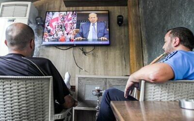 Lebanese men smoke a hookah as they watch a televised speech by President Michel Aoun, at a cafe in the capital Beirut on October 24, 2019, as Aoun addresses demonstrators on the eighth day of protests against tax increases and official corruption. (Photo by IBRAHIM  AMRO / AFP)