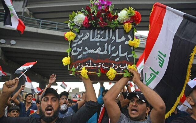 "Iraqi protesters march with a symbolic coffin representing their country and bearing the Arabic words ""the blood of the demonstrators is the end of the corrupt, for what sin have you killed me?"" as they march during an anti-government demonstration in the central holy shrine city of Najaf on October 25, 2019. (AFP)"
