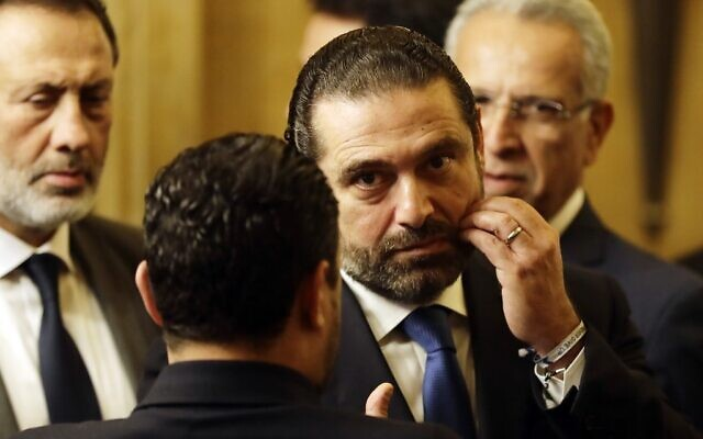Lebanon's then Prime Minister Saad Hariri speaks to an unidentified man during a press conference at his residence in downtown Beirut, November 13, 2018. (Joseph Eid/AFP)