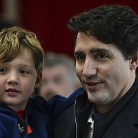 Canadian Prime Minister Justin Trudeau, accompanied by his youngest son Hadrien Trudeau, waits in line to cast his vote on election day at a polling station on October 21, 2019 in Montreal, Canada. (Minas Panagiotakis/Getty Images/AFP)