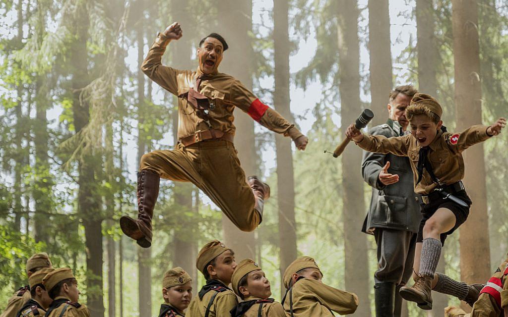 "Taika Waititi, center, wrote and directed ""Jojo Rabbi."" Roman Griffin Davis, jumping to his right, co-stars. (Kimberley French/Twentieth Century Fox Film Corp. via JTA)"