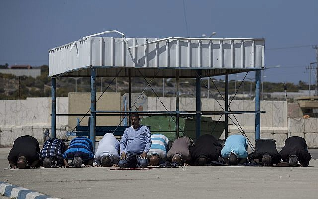 In this photo from March 26, 2017, Palestinian residents of the Gaza Strip pray as they wait on the Israeli side of the Erez terminal to cross into Gaza. (AP Photo/Tsafrir Abayov, File)