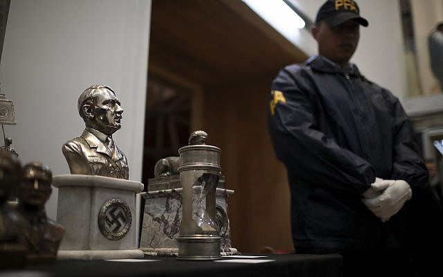 A police officer stands in front of a cache of Nazi artifacts discovered in 2017, during a press conference in Buenos Aires, Argentina, October 2, 2019. (Natacha Pisarenko/AP)