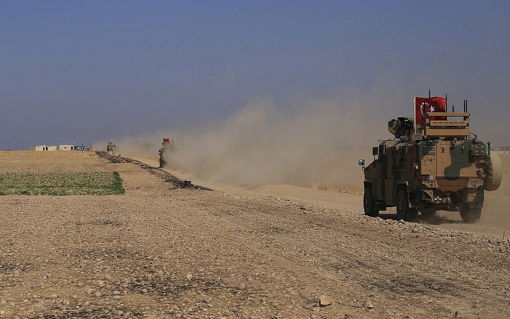 "A Turkish armored vehicle patrols with American forces in the so-called ""safe zone"" on the Syrian side of the border with Turkey, near the town of Tal Abyad, northeastern Syria, October 4, 2019. (AP Photo/Baderkhan Ahmad)"