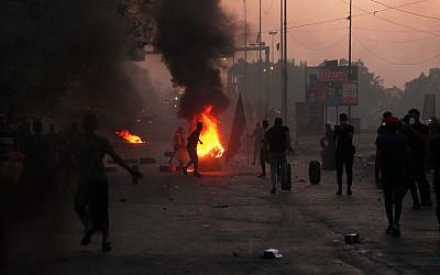 Anti-government protesters set fires and close a street during a demonstration in Baghdad, Iraq, October 5, 2019. (AP Photo/Hadi Mizban)