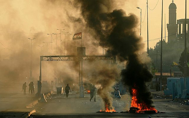 Iraqi security forces fire tear gas to disperse anti-government protesters who set fires and close a street during a demonstration in Baghdad, Iraq on October 5, 2019. (AP/Hadi Mizban)