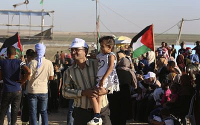 In this Sept. 25, 2019 photo, Palestinian activist Ahmed Abu Artima holds his daughter during an alternative protest he organized near the separation fence between the Gaza Strip and Israel, east of Gaza City. (AP Photo/Adel Hana)
