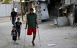 In this Wednesday, Oct. 2, 2019 photo, a Palestinian amputee Ziad al-Madani, who lost his leg when he was shot by Israeli troops during a protest on the border, walks on the main street of Khan Younis, Gaza Strip. (AP Photo/Adel Hana)