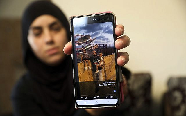 A relative on October 7, 2019, shows a photo of Ahmed Manaa with his children at the family home in Majd al-Krum, Israel. Two brothers, Ahmed and Khalil Manaa, and a third man, Mohammed Sabea, were killed in a midday shootout in Majd al-Krum, that left another Manaa brother wounded. (AP Photo/Mahmoud Illean)