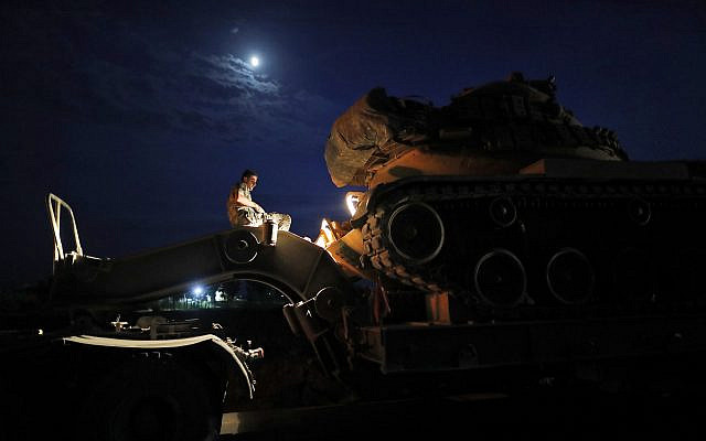 A Turkish army officer prepares to upload a tank from a truck to its new position on the Turkish side of the border between Turkey and Syria, in Sanliurfa province, southeastern Turkey, Tuesday, Oct. 8, 2019. . (AP Photo/Lefteris Pitarakis)