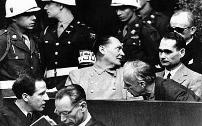 In this photo from March 27, 1946, Nazi German foreign minister Joachim von Ribbentrop, right, leans in front of Rudolf Hess, Hitler's deputy, to confer with his lawyer, lower left, while Hermann Goering, center, chief of the German air force and one of Hitler's closest aides, turns to talks with Karl Doenitz, rear right, during the Nueremberg war crime trial session. (AP Photo, File)