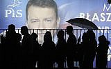 In this photo taken on September 26, 2019, supporters of Poland's ruling right-wing party are standing in line before a candidate's billboard to get to a party convention in Warsaw, Poland, ahead of the parliamentary election in which the Law and Justice party is hoping to win a second term in power. (AP/Czarek Sokolowski)