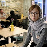 In this October 7, 2019 photo, 21-year-old Afghan refugee Fatemeh Jafari poses for a photo at her basement Tehran coffee shop, in downtown Tehran, Iran. (AP Photo/Ebrahim Noroozi)
