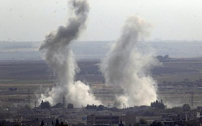 Photo taken from the Turkish side of the border between Turkey and Syria, in Ceylanpinar, Sanliurfa province, southeastern Turkey, showing smoke billowing from targets in Ras al-Ayn, Syria, caused by bombardment by Turkish forces, October 15, 2019. (AP Photo/Cavit Ozgul)
