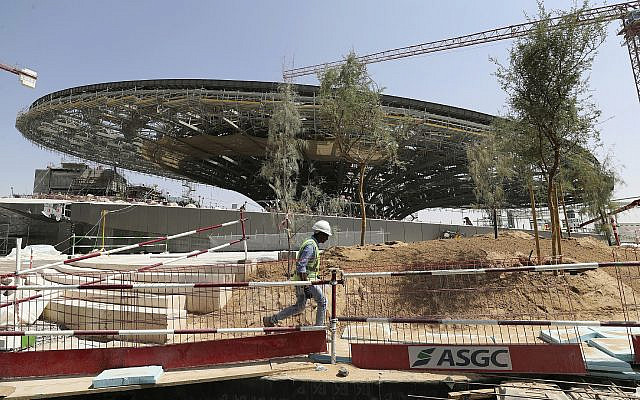 In this Oct. 8, 2019, photo, a worker passes in front of the Sustainability Pavilion at the under construction site of the Expo 2020 in Dubai, United Arab Emirates. (AP Photo/Kamran Jebreili)