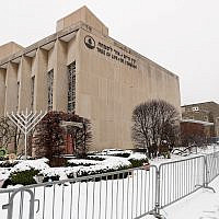 In this Monday, Feb. 11, 2019 file photo, a woman passes by the Tree of Life Synagogue in Pittsburgh's Squirrel Hill neighborhood.  (AP Photo/Keith Srakocic)