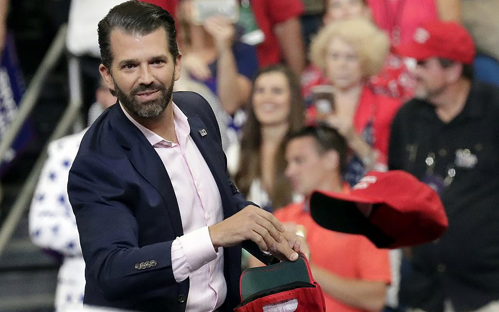 In this June 18, 2019, file photo, Donald Trump Jr. throws hats to supporters at a campaign rally for President Donald Trump in Orlando, Fla. (AP Photo/John Raoux)