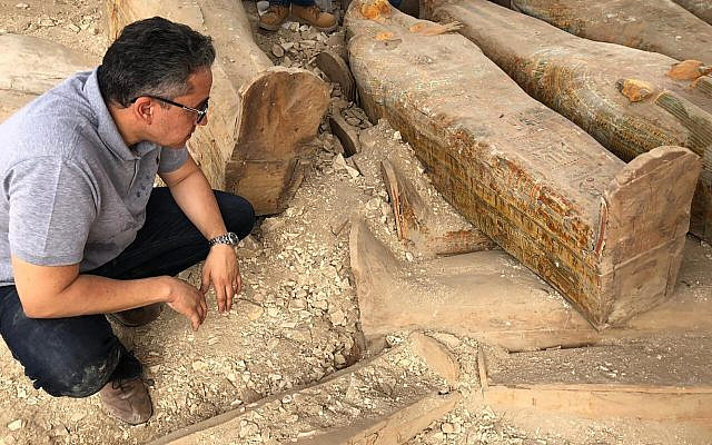 Egyptian Minister of Antiquities Khaled el-Anany looking at recently discovered ancient colored coffins with inscriptions and paintings, in the southern city of Luxor, Egypt, October 15, 2019. (Egyptian Ministry of Antiquities via AP, File)
