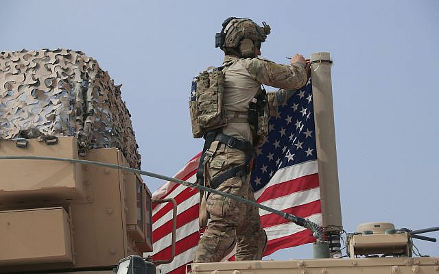 American soldier mount the U. flag on a vehicle near the town of Tel Tamr, north Syria, Sunday, Oct. 20, 2019. Kurdish-led fighters and Turkish-backed forces clashed sporadically Sunday in northeastern Syria amid efforts to work out a Kurdish evacuation from a besieged border town, the first pull-back under the terms of a US-brokered cease-fire. (AP Photo/Baderkhan Ahmad)