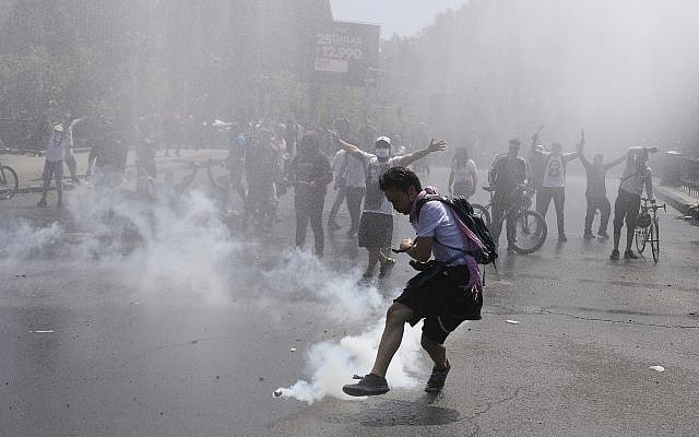 A protester kicks a tear gas canister during clashes with police in Santiago, Chile, October 20, 2019. (AP Photo/Esteban Felix)